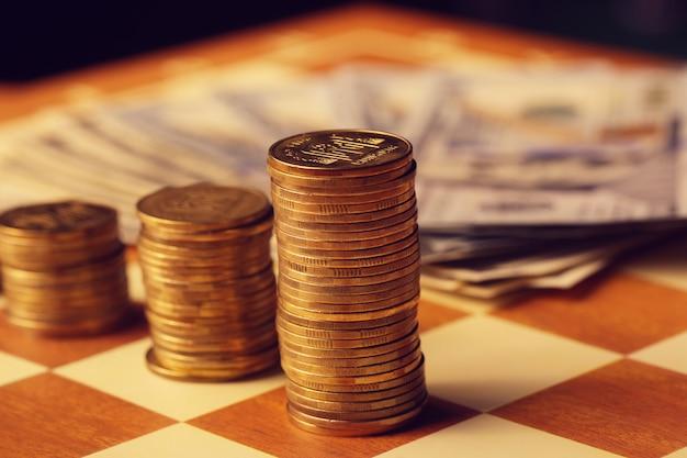Una pila de monedas surtidas en la mesa de madera
