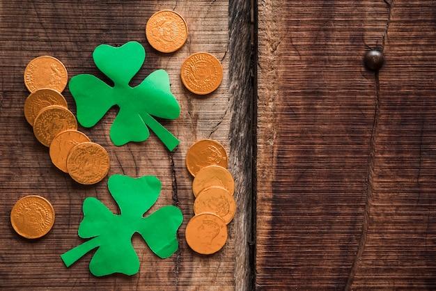 Pila de monedas y tréboles de papel verde en mesa de madera