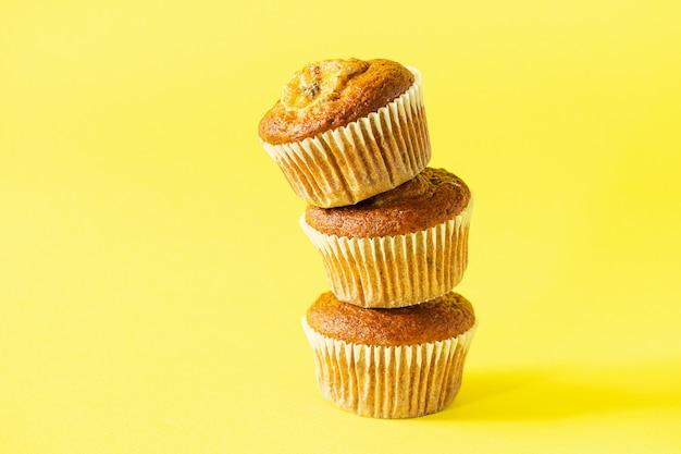 Pila de muffins de plátano sobre un fondo amarillo. postre vegano saludable.