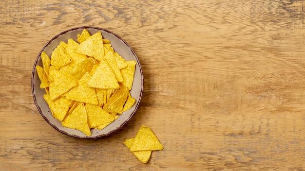 Pila de nachos en plato sobre mesa de madera
