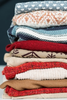 Pila de nuevos suéteres y jerséis de lana y algodón preparados para los fríos días de otoño e invierno