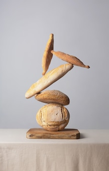 Pila de pan de equilibrio sobre una mesa cubierta con un mantel sobre un fondo gris