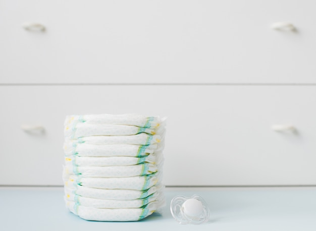 Pila de pañales contra un armario blanco