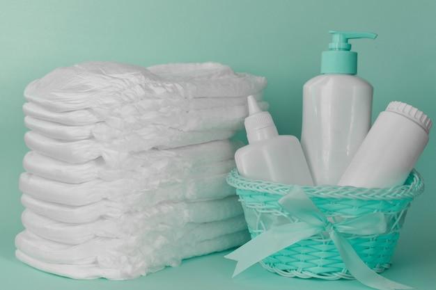 Una pila de pañales limpios, modernos y secos y una canasta de higiene sobre un fondo turquesa.