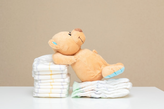 Pila de pañales con osito de peluche acostado sobre una mesa blanca, para baby shower con espacio de copia