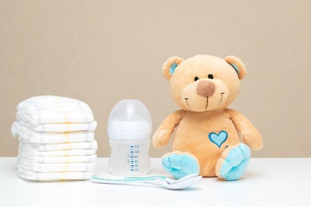 Pila de pañales con osito de peluche y botella de leche - listo para baby shower con espacio de copia.