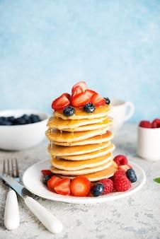 Pila de panqueques americanos con miel y fresas