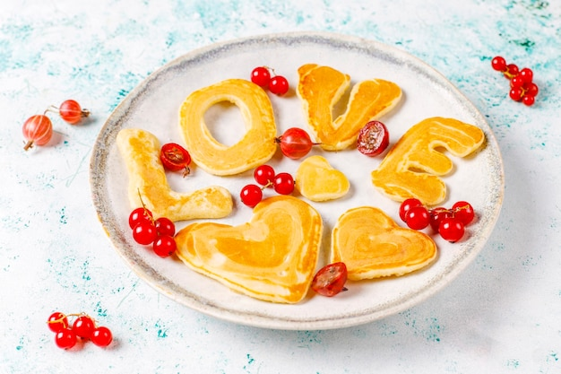 Pila de panqueques caseros con jarabe de miel y bayas.