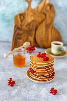 Pila de panqueques caseros con miel y bayas