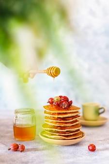 Pila de panqueques caseros con miel y bayas.