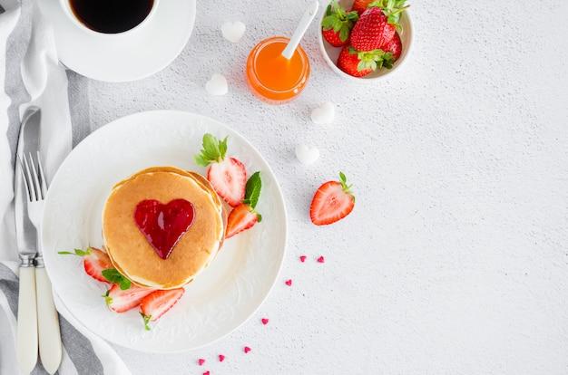 Una pila de panqueques con un corazón de mermelada encima con fresas frescas