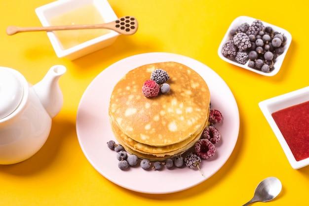 Una pila de panqueques en un plato rosado con bayas junto a mermelada de fresa y miel