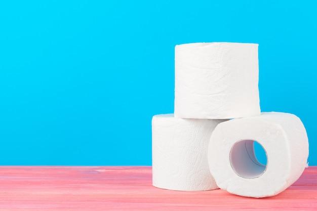 Pila de papel higiénico sobre fondo azul brillante