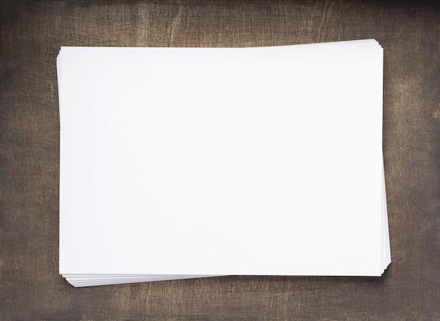 Pila de papel con páginas vacías sobre fondo de madera, vista superior