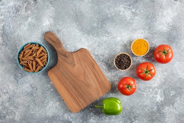 Pila de pasta dietética marrón sobre fondo gris con verduras y especias.