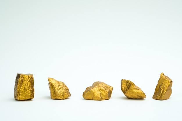 Una pila de pepitas de oro o mineral de oro sobre fondo blanco
