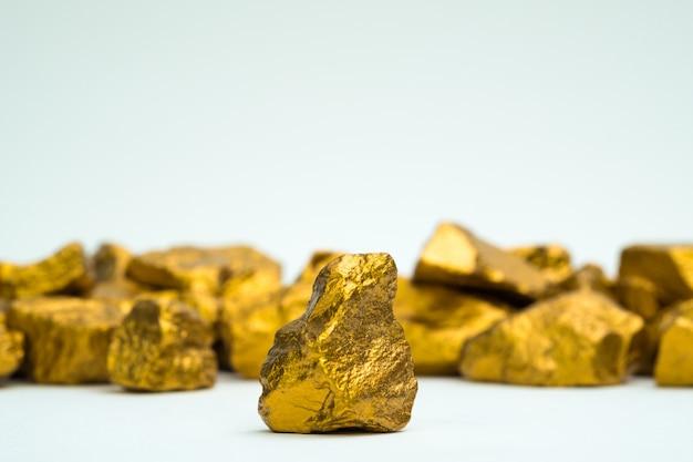 Una pila de pepitas de oro o mineral de oro sobre fondo blanco,