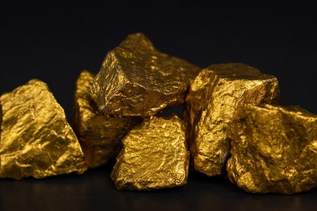 Una pila de pepitas de oro o mineral de oro sobre fondo negro