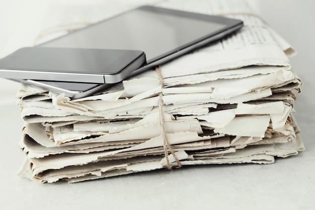Pila de periódicos con tableta digital y teléfono inteligente