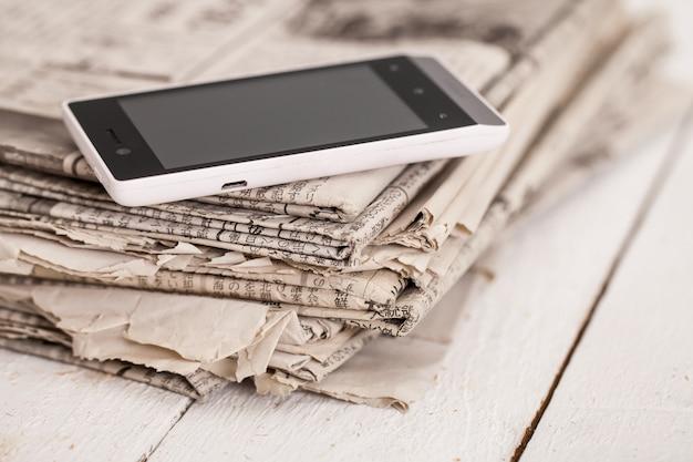 Pila de periódicos con teléfono inteligente