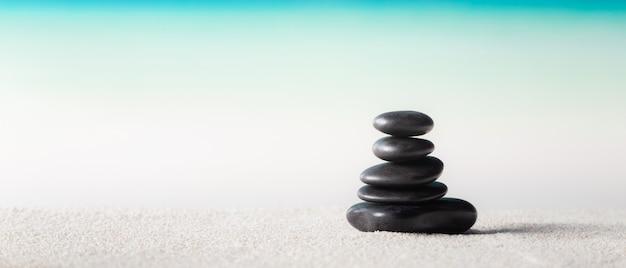 Pila de piedras zen en la playa de arena