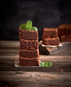 Pila de piezas cuadradas de pastel de brownie al horno sobre una tabla de madera