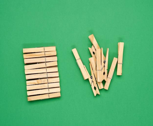 Pila de pinzas de madera sobre la superficie verde, vista superior, cero residuos