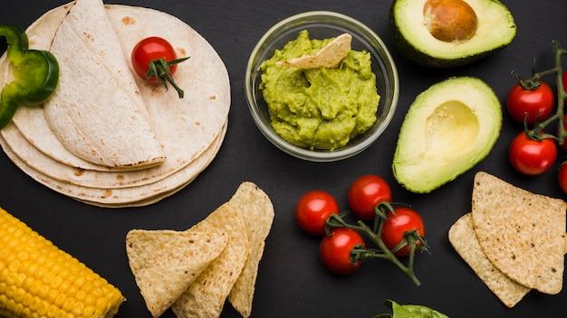 Pila de pita al lado de verduras y salsa con nachos.