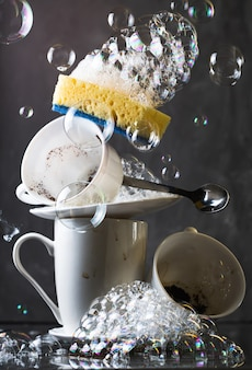 Pila de platos blancos sucios sobre fondo oscuro, con esponja de lavado y burbujas
