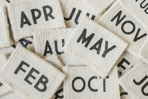 La pila del primer de pequeño calendario de la tela en muchos meses texturizó el fondo