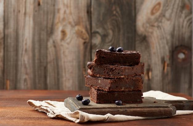 Pila de rebanadas cuadradas de pastel de chocolate brownie con nueces sobre una superficie de madera