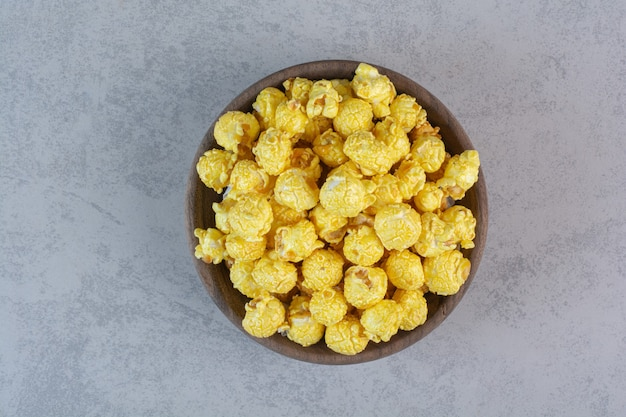 Pila recubierta de caramelo amarillo de palomitas de maíz en mármol.