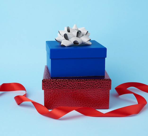 Pila de regalos envueltos con lazos anudados sobre una superficie azul