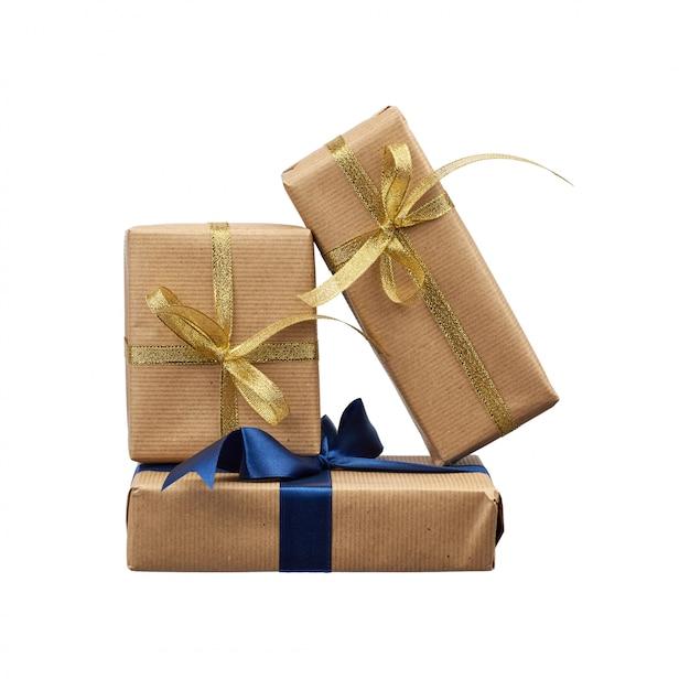 Pila de regalos envueltos en papel kraft marrón y atados con una cinta de seda azul y dorada