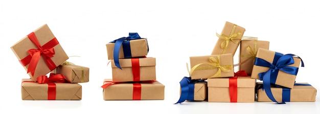 Pila de regalos envueltos en papel kraft marrón y atados con cinta de seda azul y roja, cajas aisladas