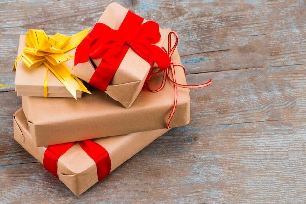 Pila de regalos en papel kraft con cinta de raso roja sobre fondo de madera con espacio de copia.