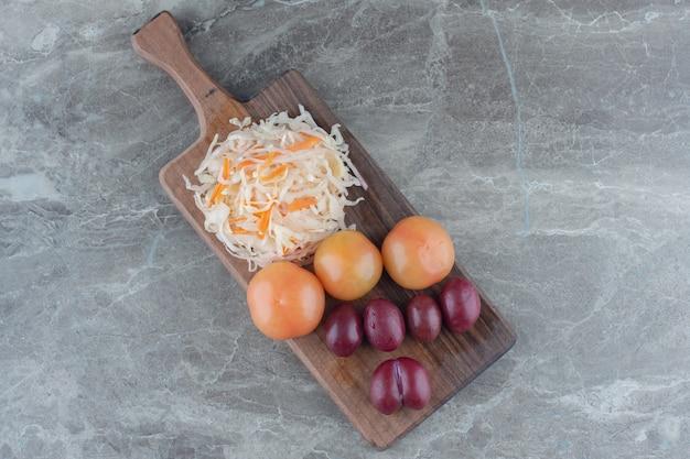 Pila de repollo fermentado sabroso con verduras sobre tabla de cortar de madera.
