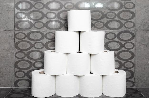 Pila de rollos de papel higiénico en estante en el baño.