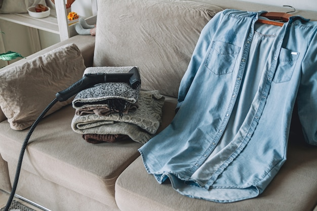 Una pila de ropa de abrigo limpia y camisa con limpiador a vapor en el sofá