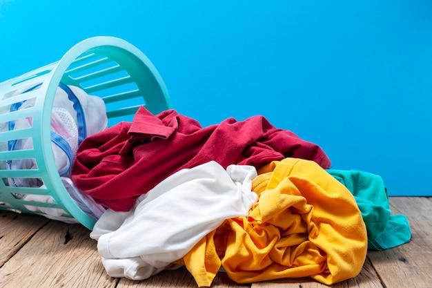 Pila de ropa sucia en la cesta de lavado en madera