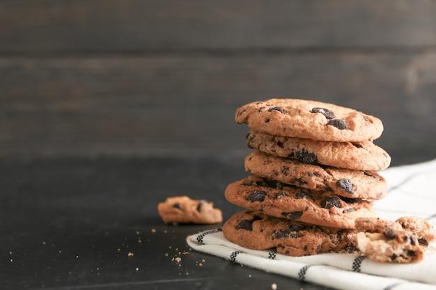 Pila de sabrosas galletas de chispas de chocolate en servilleta y fondo de madera. espacio para texto
