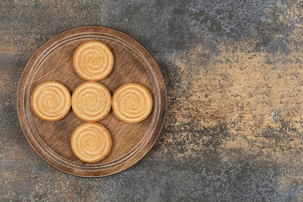 Pila de sabrosas galletas en placa de madera.