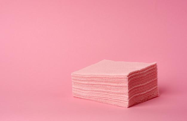 Pila de servilletas cuadradas plegables rosadas desechables de papel en un espacio rosado