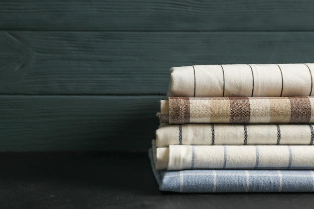 Pila de servilletas de tela en mesa negra, espacio para texto
