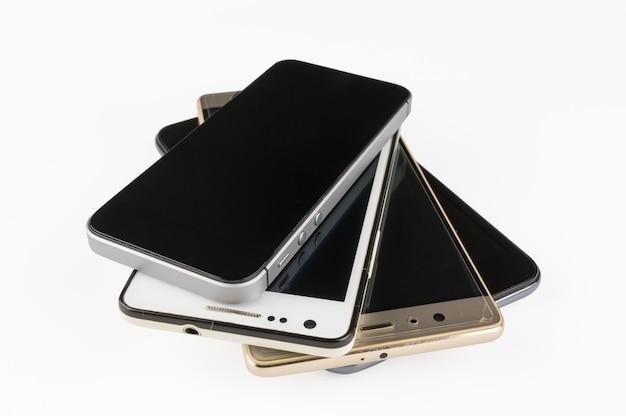 Pila de smartphones de gama alta en el escritorio blanco.