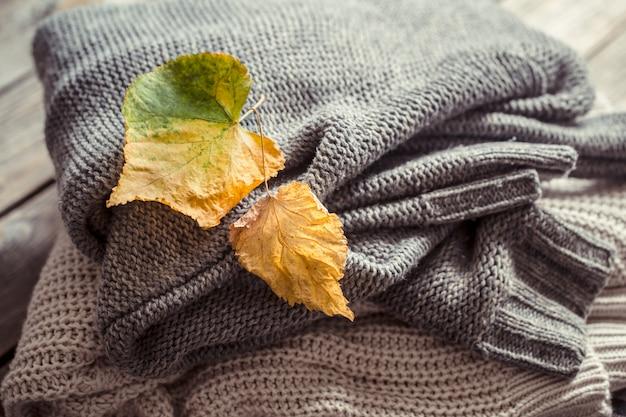 Una pila de suéteres y hojas de otoño