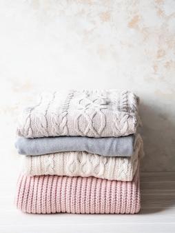 Pila de suéteres de lana de punto cálido tonos pastel contra la pared con textura de color beige. copia espacio