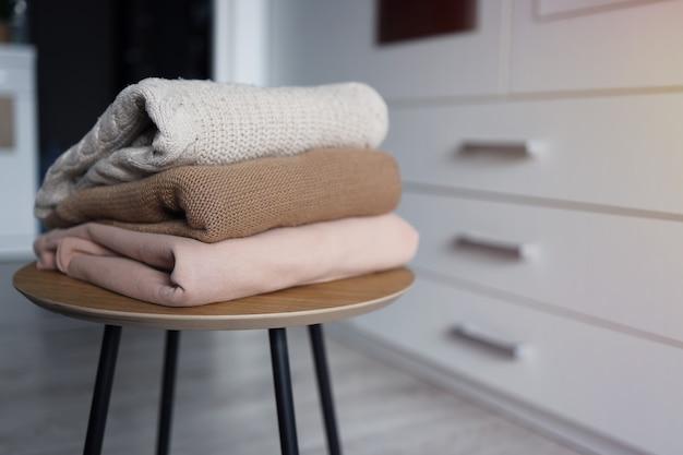 Pila de suéteres de punto acogedor sobre una mesa de madera. estilo retro. concepto cálido