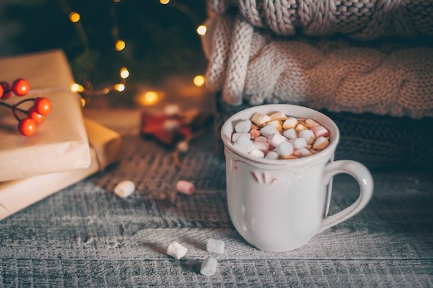 Pila de suéteres de punto acogedor y taza de chocolate caliente con malvavisco