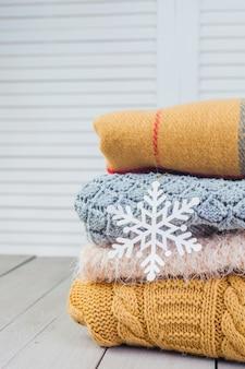 Pila de suéteres de punto acogedoras blancas en una mesa de madera